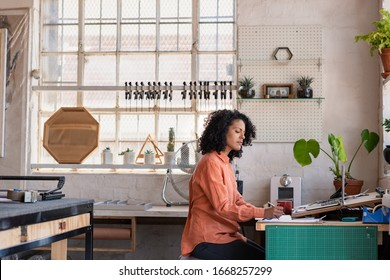 Young woman working on a laptop and writing notes while sitting at a table in her picture framing studio