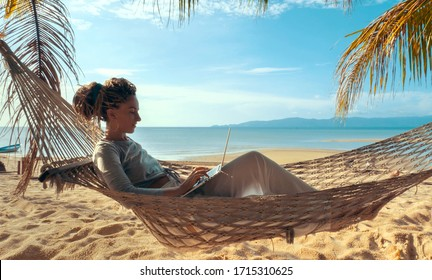 Young woman working on laptop lying in hammock at sand beach of tropical island. Freelance outdoor work concept