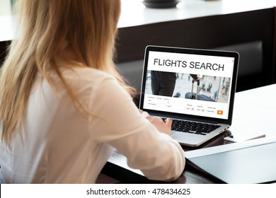 Young woman working on laptop computer, searching for flight using online web service. Attractive female booking round trip airplane ticket on website. Rear view over the shoulder. Focus on screen