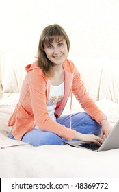 Young woman working on laptop on the bed