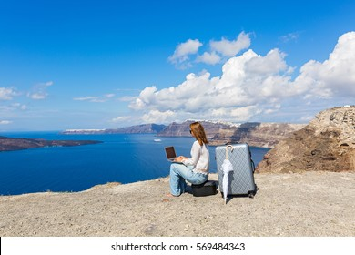 Young woman working on laptop on the seafront