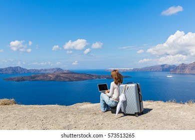 Young woman working on laptop on the seafront, Santorini island, Greece
