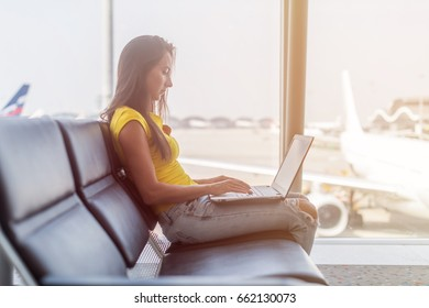Young woman working on laptop sitting in a departure lounge of airport