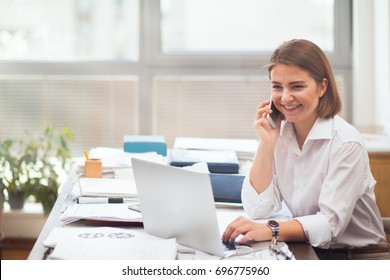 Young woman working on laptop and smiling