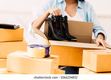 Young woman working online shopping and packing shoes with cardboard box on bed at home - Business online shipping and delivery concept