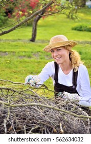 Young woman working in orchard, after tree pruning, pile of cut branches and twigs of fruit trees, cutting branches of apple trees in garden, smiling woman piling up brushwood in spring
