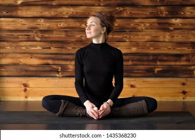 Young woman working out doing yoga or pilates exercise, sitting in baddha konasana, bound angle or butterfly pose. Full length shot
