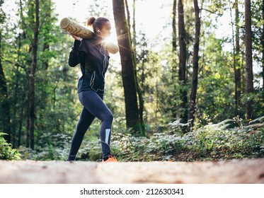 Young woman working out in forrest lifting weights