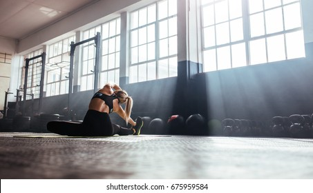 Young woman working out in gym. Back view of woman doing stretching exercise in the morning sunlight at the gym.