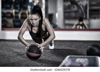 Young woman working out with medicine ball in the gym