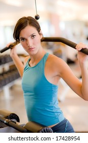 A young woman working out on a machine in a gym