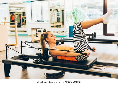 Young woman working out on a pilates reformer