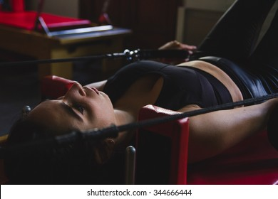 Young woman working out on a pilates machine