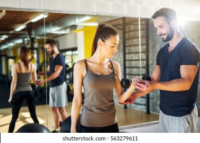 Young woman working out with personal trainer at the gym.