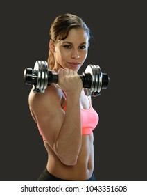 Young woman working out with weights isolated on a dark background