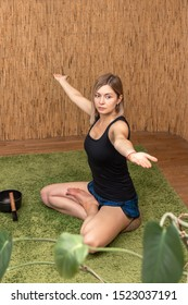 Young woman working out in yoga studio with hands to the sides and Sitting in Siddhasana, Half Lotus Posture, meditating, breathing, close-up