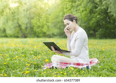A young woman is working in a park