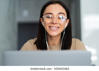 Young woman working remotely from home office on couch in kitchen behind laptop internet in headphones.