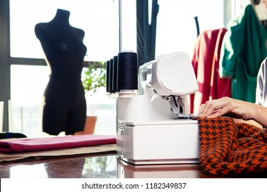 Young woman working in a sewing studio: sewing with a serger, overlocker. Fashion designers atelier