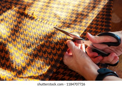 Young woman working in a sewing studio: cutting fabric with scissors. Fashion designers atelier