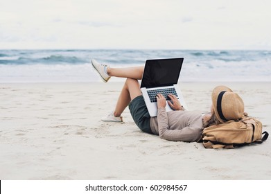 Young woman working, using laptop computer on a beach. Freelance work, vacations, distance work, social distancing, e-learning, connection, creative professional, new business, meeting online concept
