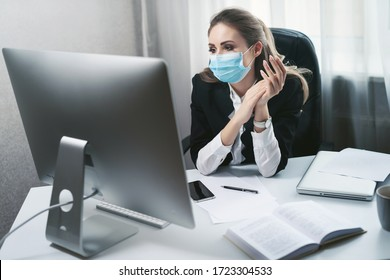 A young woman works in a home office during quarantine due to the pandemic of the coronavirus Covid-19. Girl in a disposable medical facial mask. Self-isolation to prevent infection