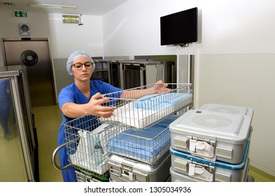 A young woman works in a hospital as a  medical hygiene assistant. She is dressed  in special medical hygiene clothing and  carries out hygiene disinfecting and logistic tasks.