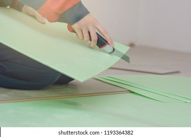 a young woman in workwear cuts a green laminate backing with a sharp blade. Insulated underlay on floor ready for the click lock wood effect laminate flooring to be laid.