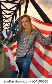 Young woman wrapped in American flag on an iron bridge at dusk of the city