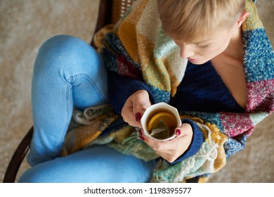 Young woman wrapped in a blanket drinking hot tea with lemon