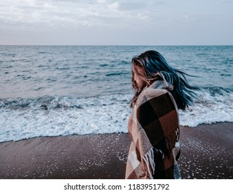Young woman wrapped in plaid walking on sand coast near the sea in windy weather.