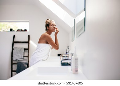 Young woman wrapped in towel looking in the mirror and applying cream on her face. Female taking care of her face skin in bathroom after bath.