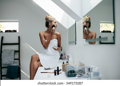 Young woman wrapped in towel with makeup brush looking to mirror at home bathroom and putting on makeup.
