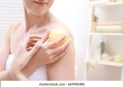 Young woman wrapped in towel and with soap in bathroom, closeup