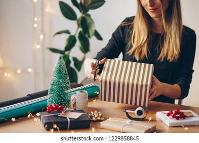 Young woman wrapping gifts for Christmas
