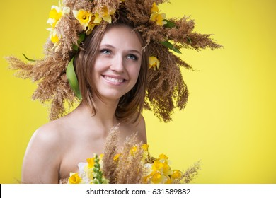 A young woman in a wreath of reeds and daffodils in, a top of the dumplings and a skirt of reeds