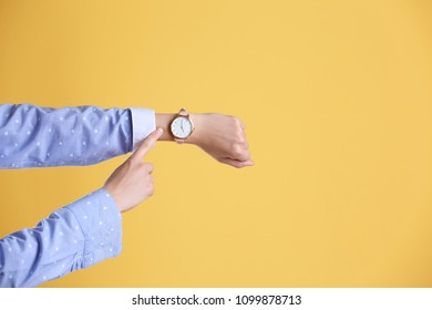 Young woman with wristwatch on color background. Time concept
