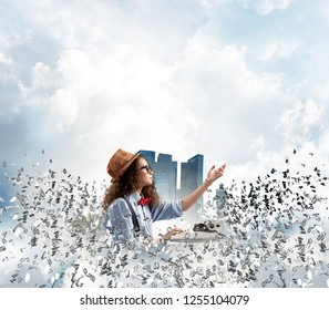 Young woman writer in hat and eyeglasses using typing machine while sitting at the table among flying letters with floating city island and cloudy skyscape on background.