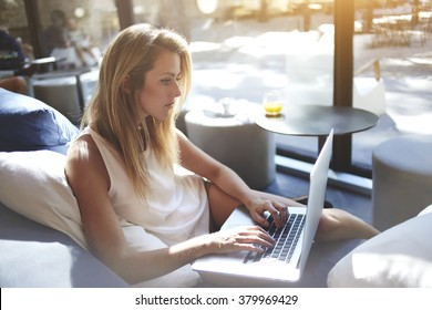 Young woman writer keyboarding text for a new book via laptop computer while sitting in co-working cafe,pretty female student searching information on net-book during lunch break in modern coffee shop