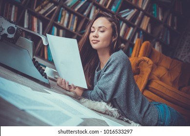 Young woman writer in library at home creative occupation reading page