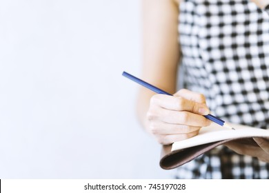Young woman writer wearing black and white dress, is writing important content idea on notebook, note, laptop with pencil. Remind schedule memory before meeting with coworker. Content concept