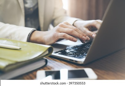 Young woman writes hands a text message on laptop keyboard with a empty blank screen monitor while having recreation time at home, person with a cup of coffee against a background of bokeh in cafe