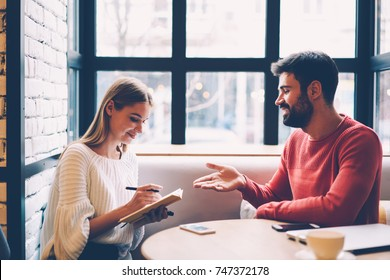 Young woman writing checklist of stuff while planning trip with boyfriend during dating in coffee shop, best friends discussing ideas for event noting in dairy while sitting together in cafe interior