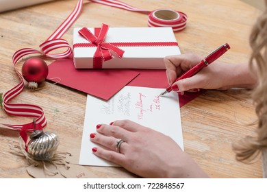young woman writing christmas cards with red nails, a red pen, and holiday decorations
