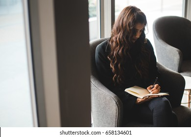 Young woman writing in coffee shop