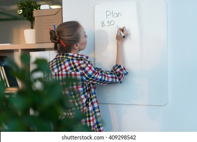 Young woman writing day plan on white board, holding marker in right hand. Student planning schedule rear view portrait.