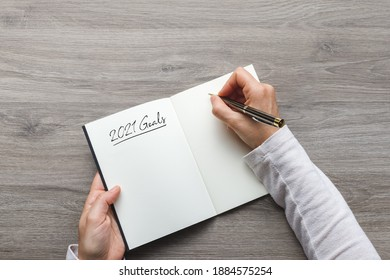 Young woman writing down her goals for the year 2021 in a notebook