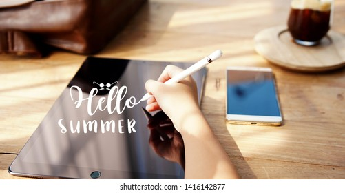 """young woman writing """"hello summer"""" on tablet"""