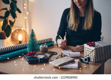 Young woman writing list of necessities for Christmas