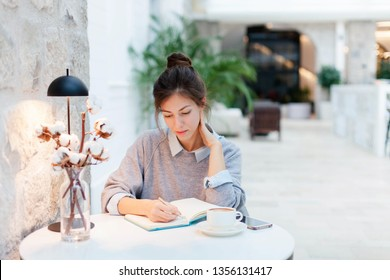 Young woman is writing in notebook in cozy cafe under warm table lamp light. Freelancer is working in comfortable coworking modern place. Girl is planning and dreaming. Wellbeing in workplace.